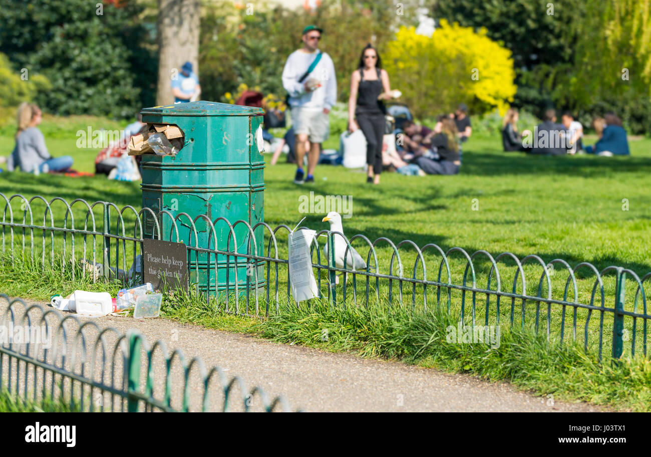 Overfull litter bin in a park at The Royal Pavilion Gardens, Brighton, East Sussex, England, UK. - Stock Image