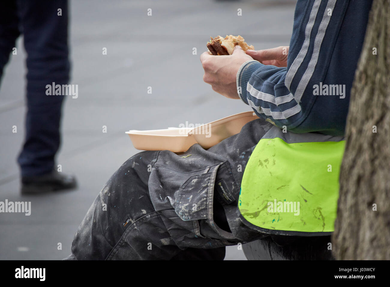 workman sitting eating burger lunch city centre Liverpool UK - Stock Image