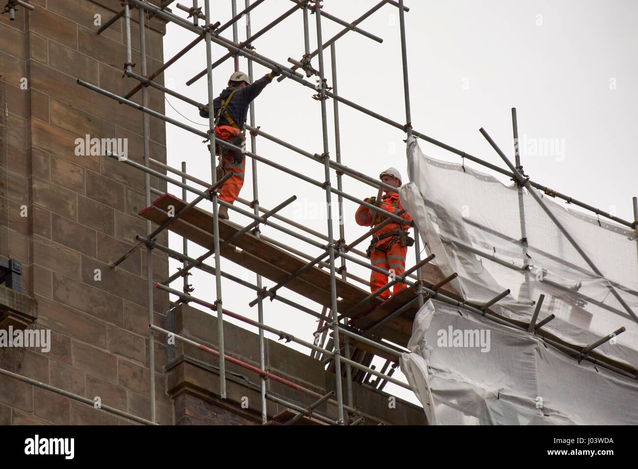 workmen with safety gear and harnesses on a high scaffold building Liverpool UK - Stock Image
