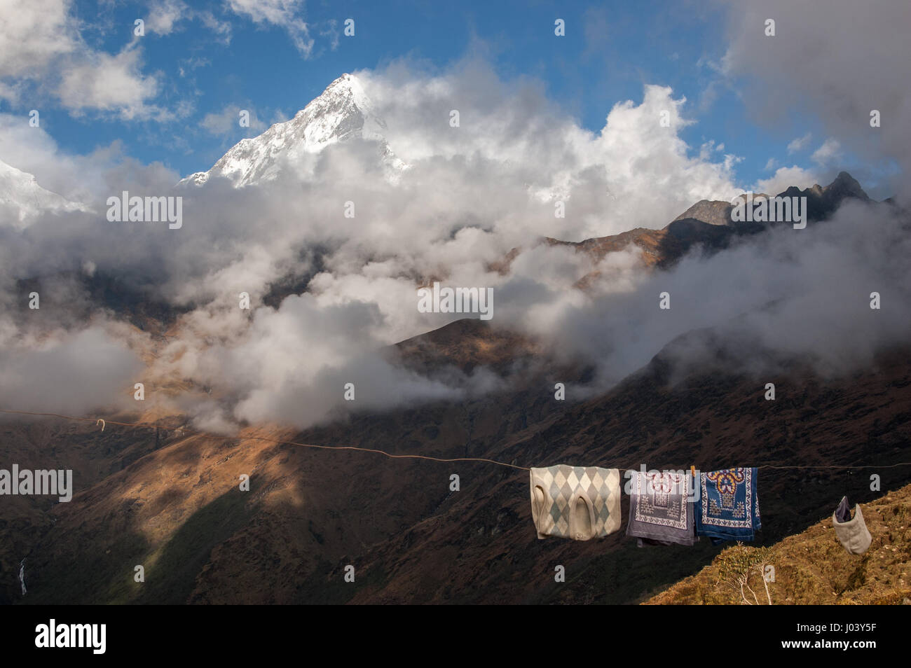 Close-up views of the Annapurnas from Kopra Ridge, Nepal; Tea-towels and a sweater hang outside to dry in the sunshine - Stock Image
