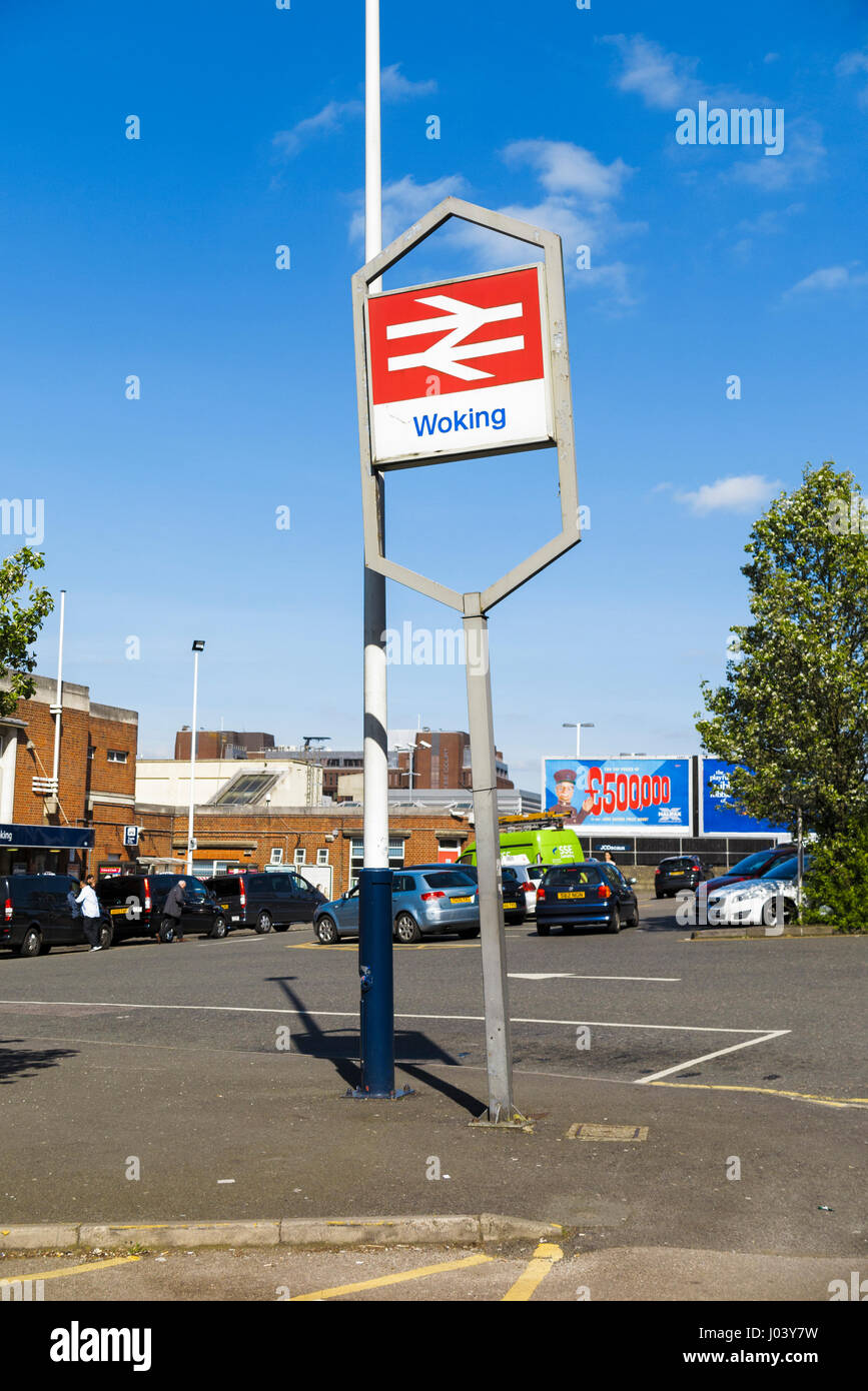 Crooked, leaning railway sign at Woking station, Woking, Surrey, south-east England, UK, sunny day with blue sky - Stock Image