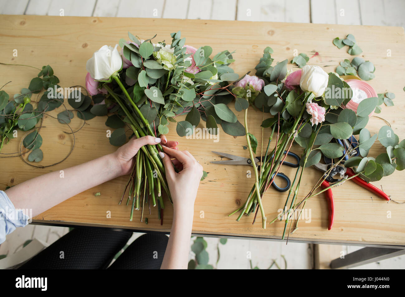 Florist at work: pretty young woman making fashion modern bouquet of different flowers - Stock Image