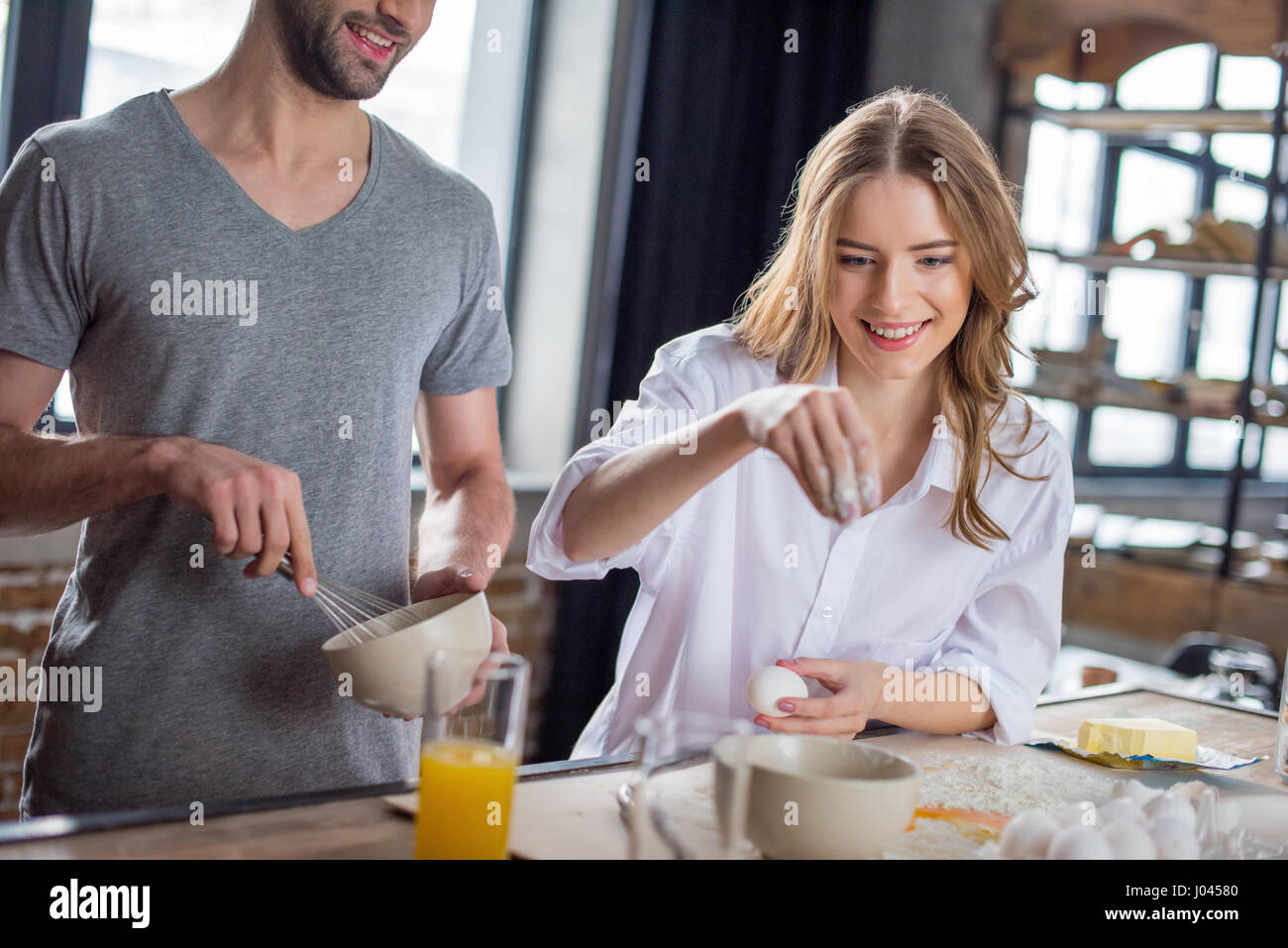 Young couple cooking together with eggs and flour in kitchen - Stock Image