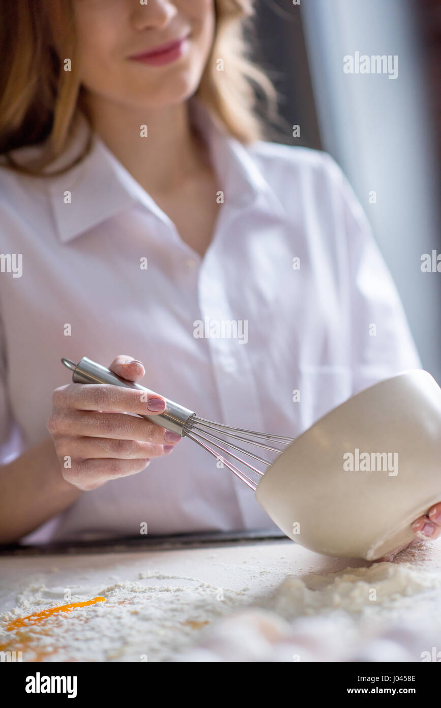 Partial view of young woman whisking eggs in bowl at kitchen - Stock Image