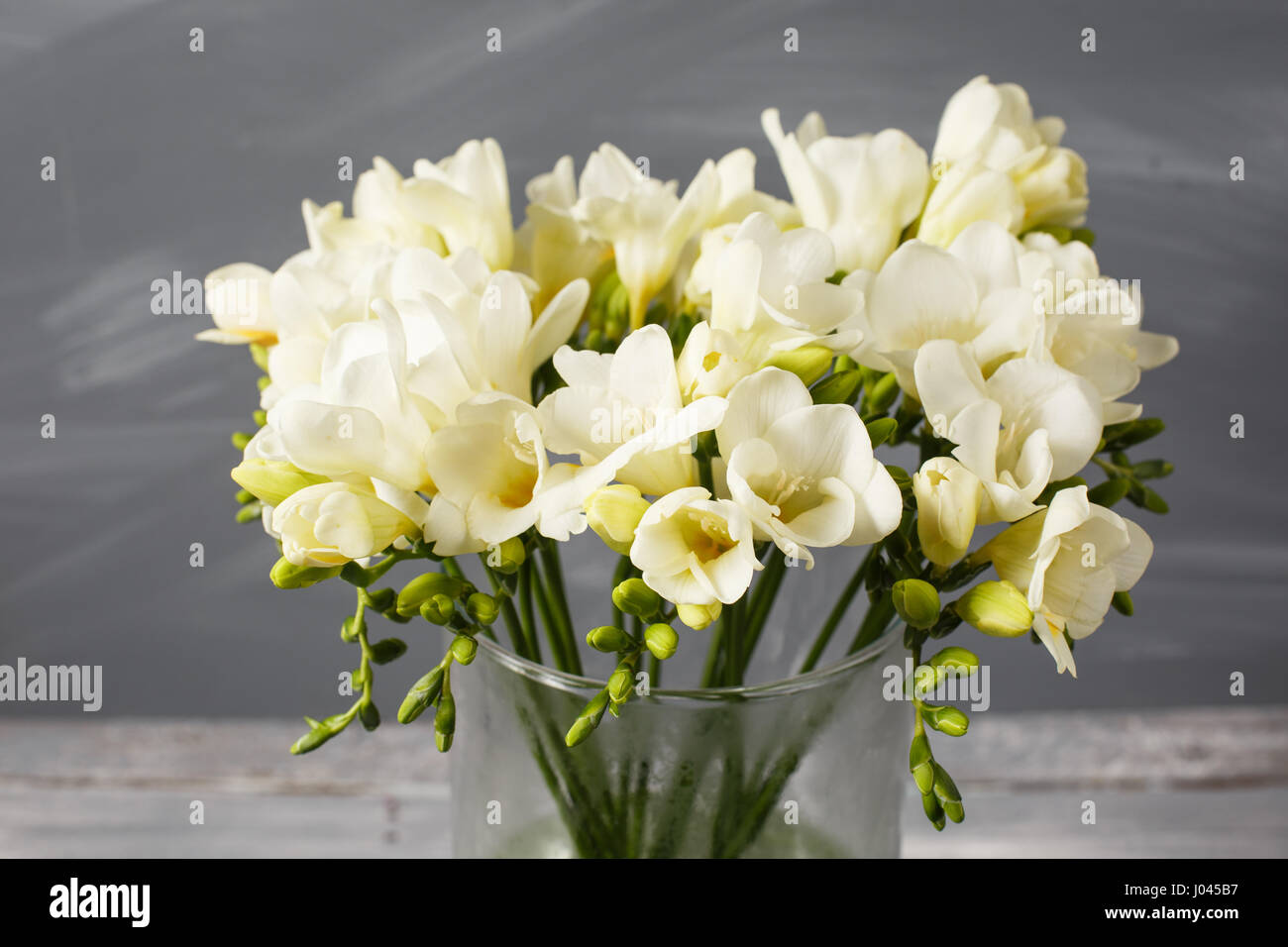 White Freesia Flowers In Decorative Vase On A Background Of Gray