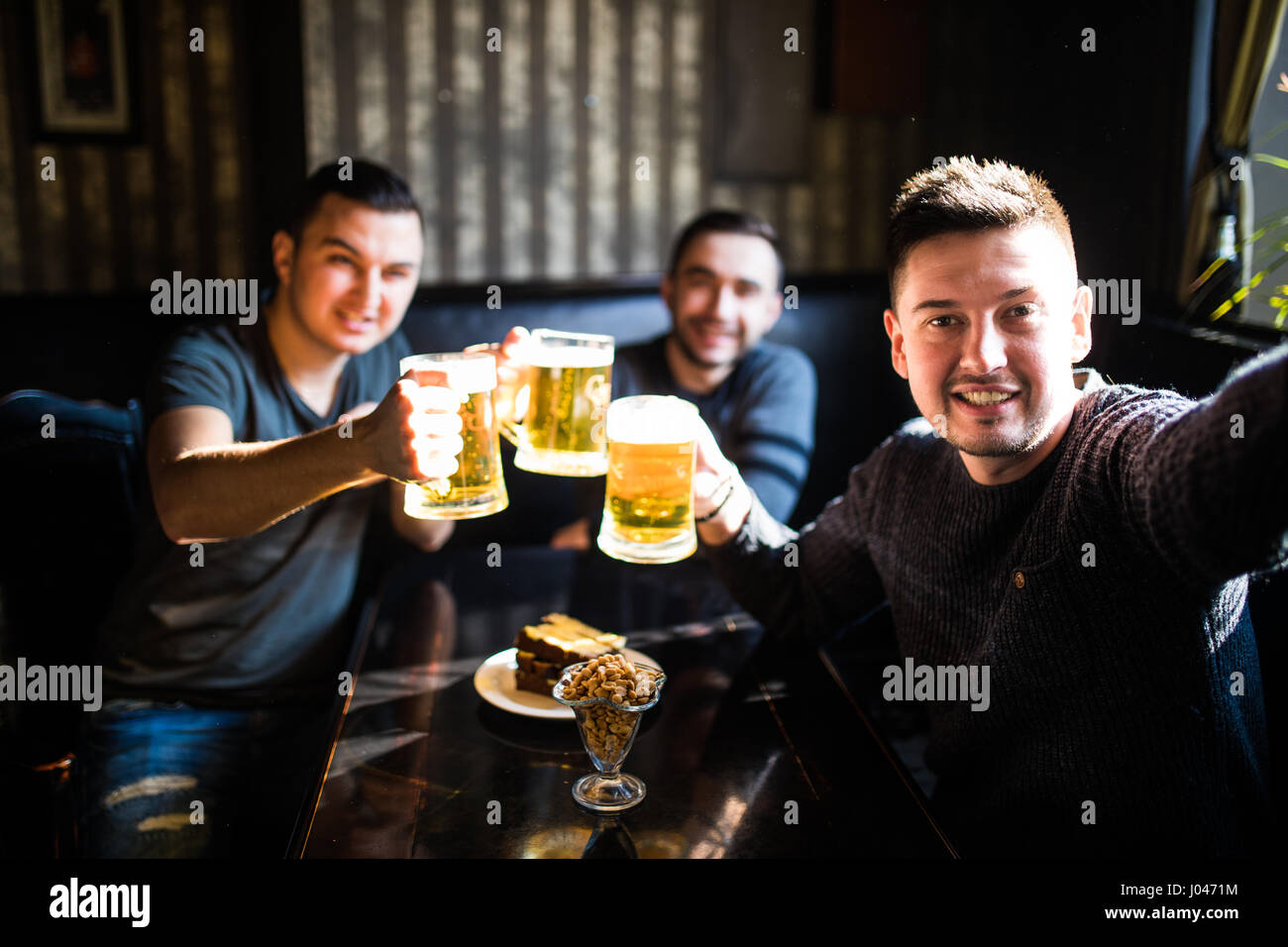 Three young men in casual clothes are taking selfie and drinking beer while sitting in pub - Stock Image