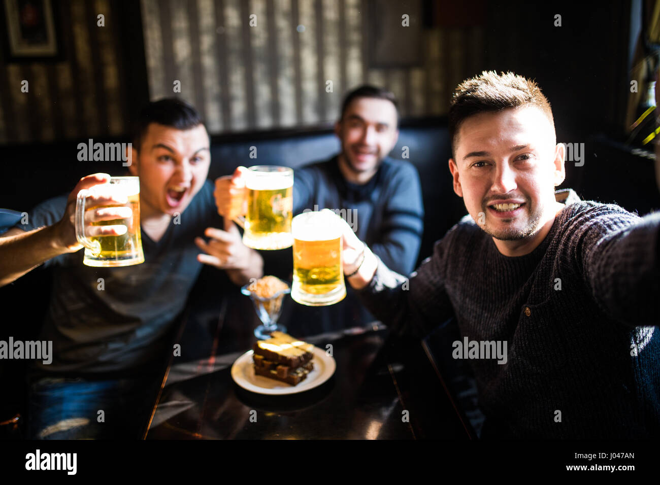 people, leisure, friendship, technology and party concept - happy male friends taking selfie and drinking beer at - Stock Image