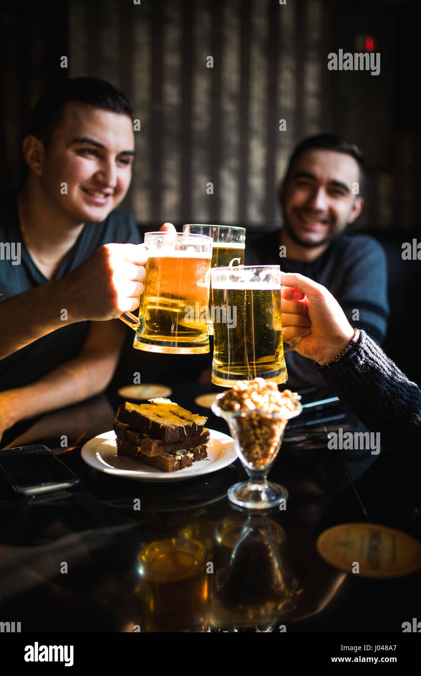 people, men, leisure, friendship and celebration concept - happy male friends drinking beer and clinking glasses - Stock Image