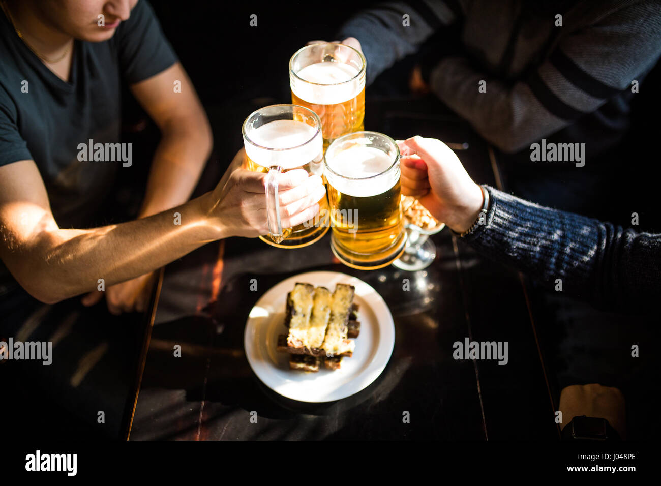 Close-up top view of people holding mugs with beer - Stock Image