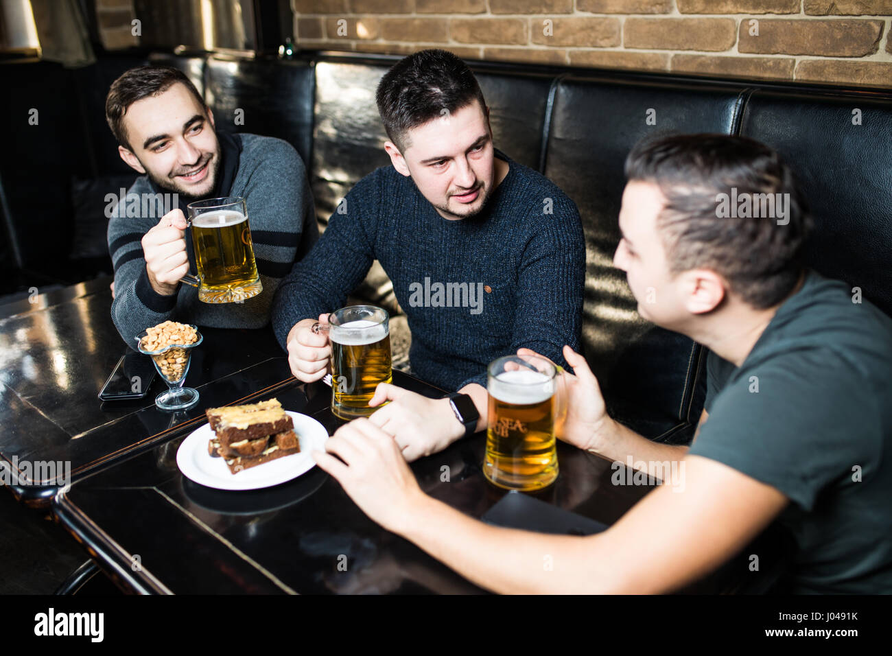 Three happy young men in casual wear talking and drinking beer while sitting in bar together - Stock Image