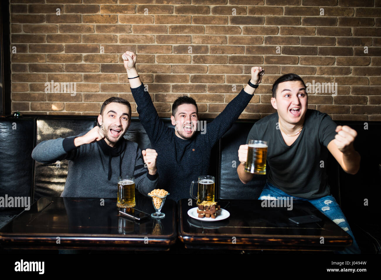 Young men drink beer, eat snaks and cheering for football. - Stock Image