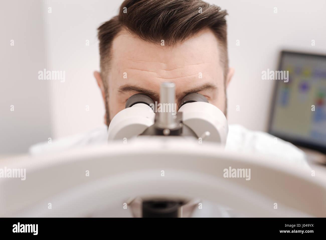 Pleasant professional ophthalmologist testing the eyesight - Stock Image