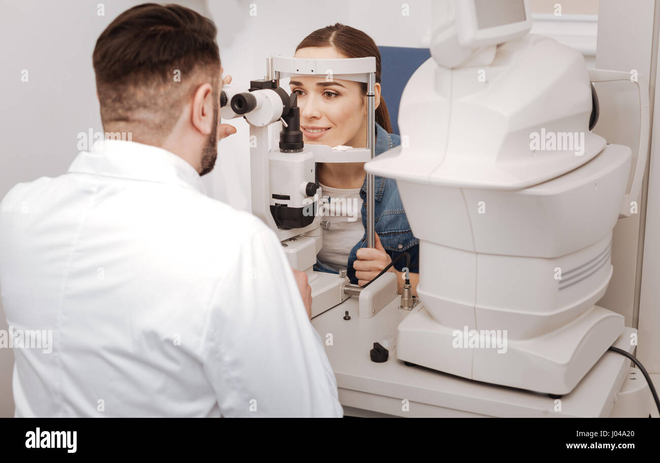 Professional male oculist sitting opposite his patient - Stock Image