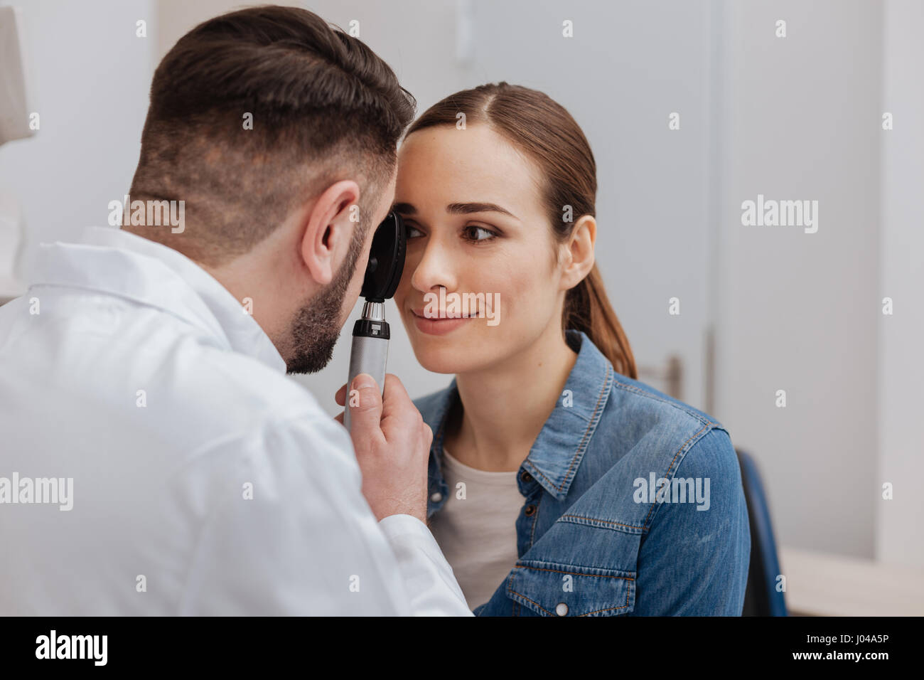 Pleasant nice doctor using ophthalmoscope - Stock Image