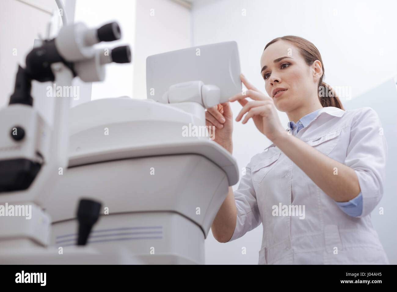 Good looking pleasant woman looking at the control panel - Stock Image