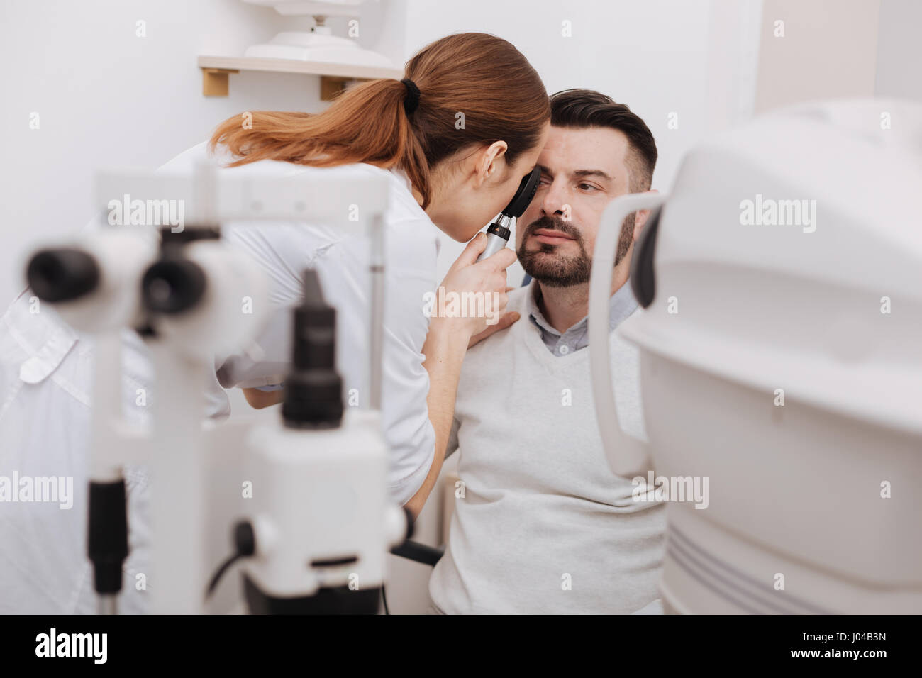 Professional experienced optometrist using an ophthalmoscope - Stock Image