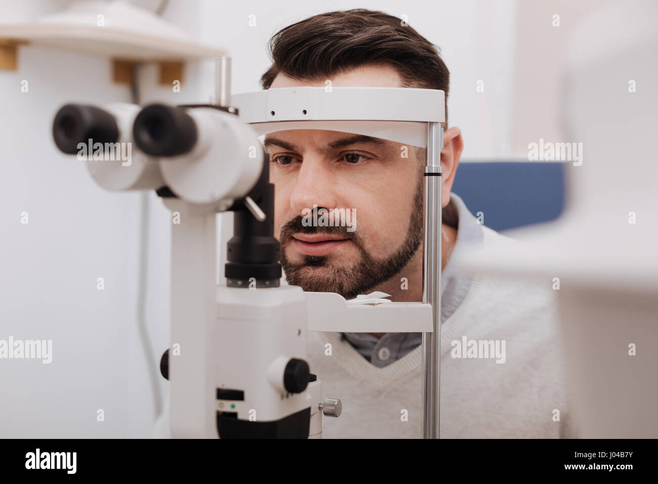 Serious handsome patient having his vision tested - Stock Image