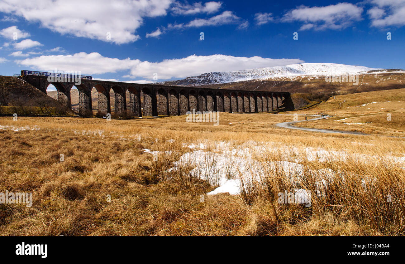 Ribblehead, England, UK - April 1, 2013: A Northern Rail Class 158 diesel passenger train passes the snow-covered - Stock Image