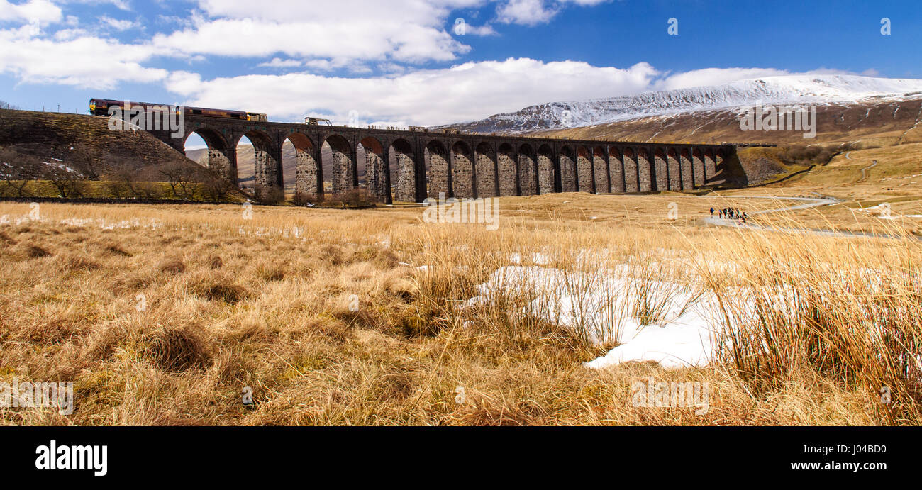 Settle, England, UK - April 1, 2013: A Northen Rail diesel passenger train crosses the landmark Ribblehead Viaduct - Stock Image