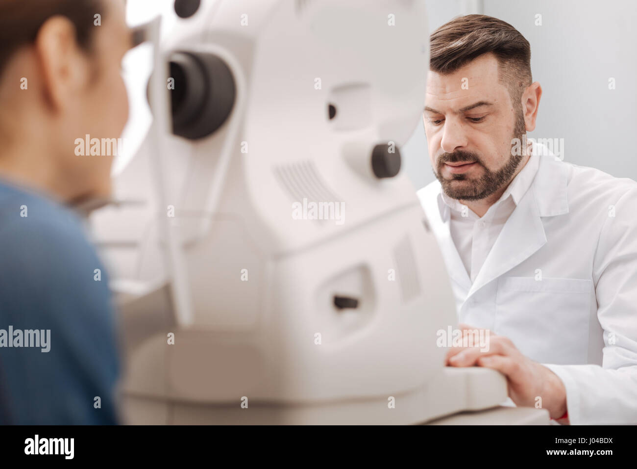 Serious male optometrist concentrating on his work - Stock Image