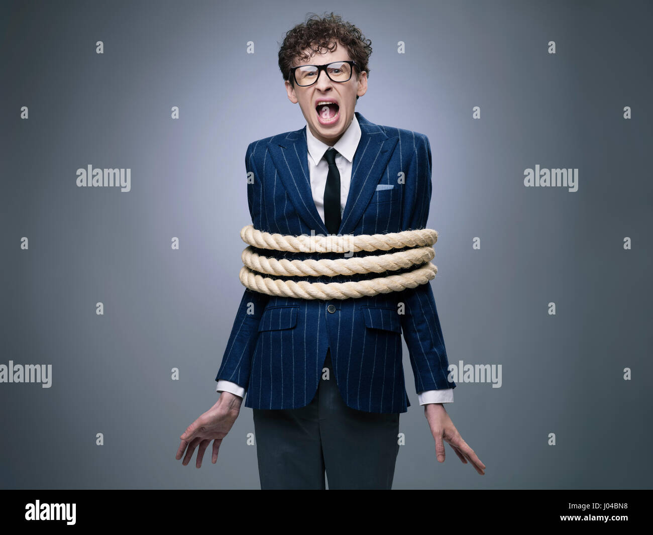 Funny business man tied up with rope screaming for help - Stock Image