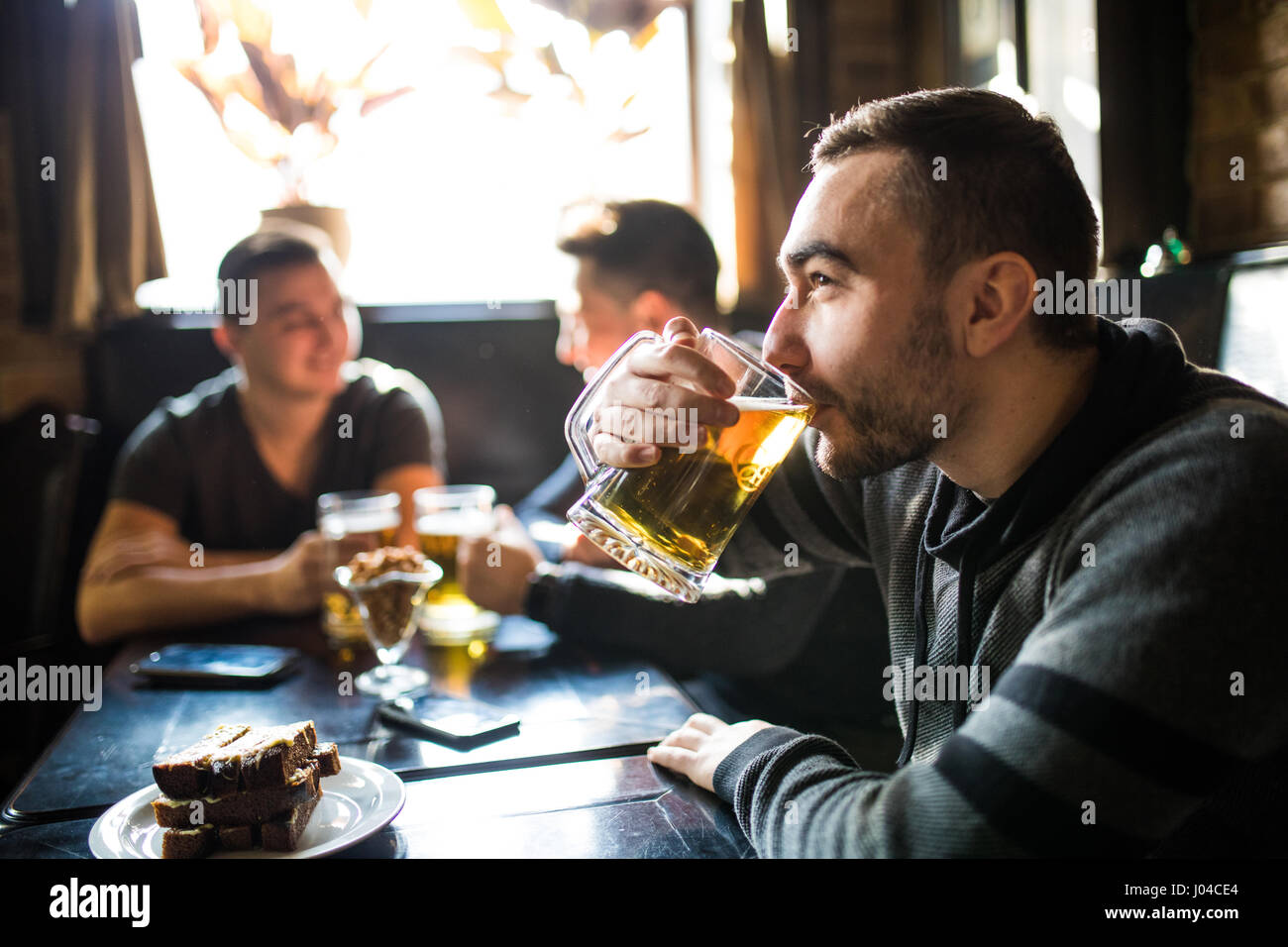 Man drink beer in front of to discussing drinking friends in pub. - Stock Image