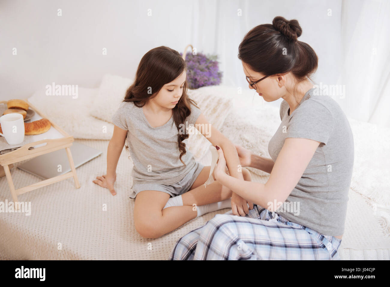 Young mother bandaging her child elbow at home - Stock Image