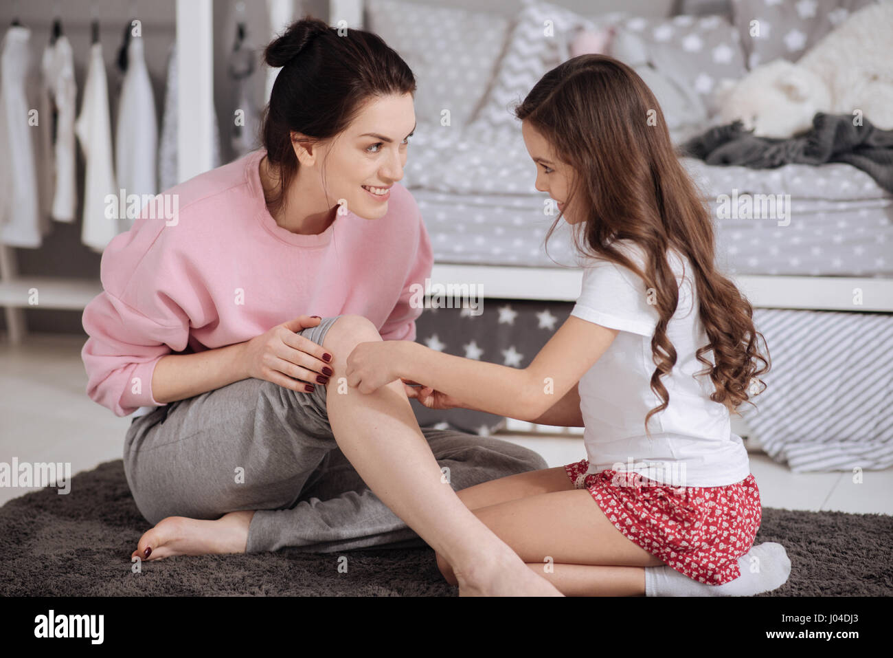 Priceless moments of motherhood. Cute skilled caring kid sitting in the night nursery and taking care of her mother - Stock Image