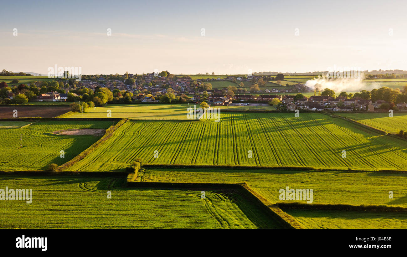 The village of Milbourne Port nestled amongst fields of crops and pasture in south Somerset, England. - Stock Image