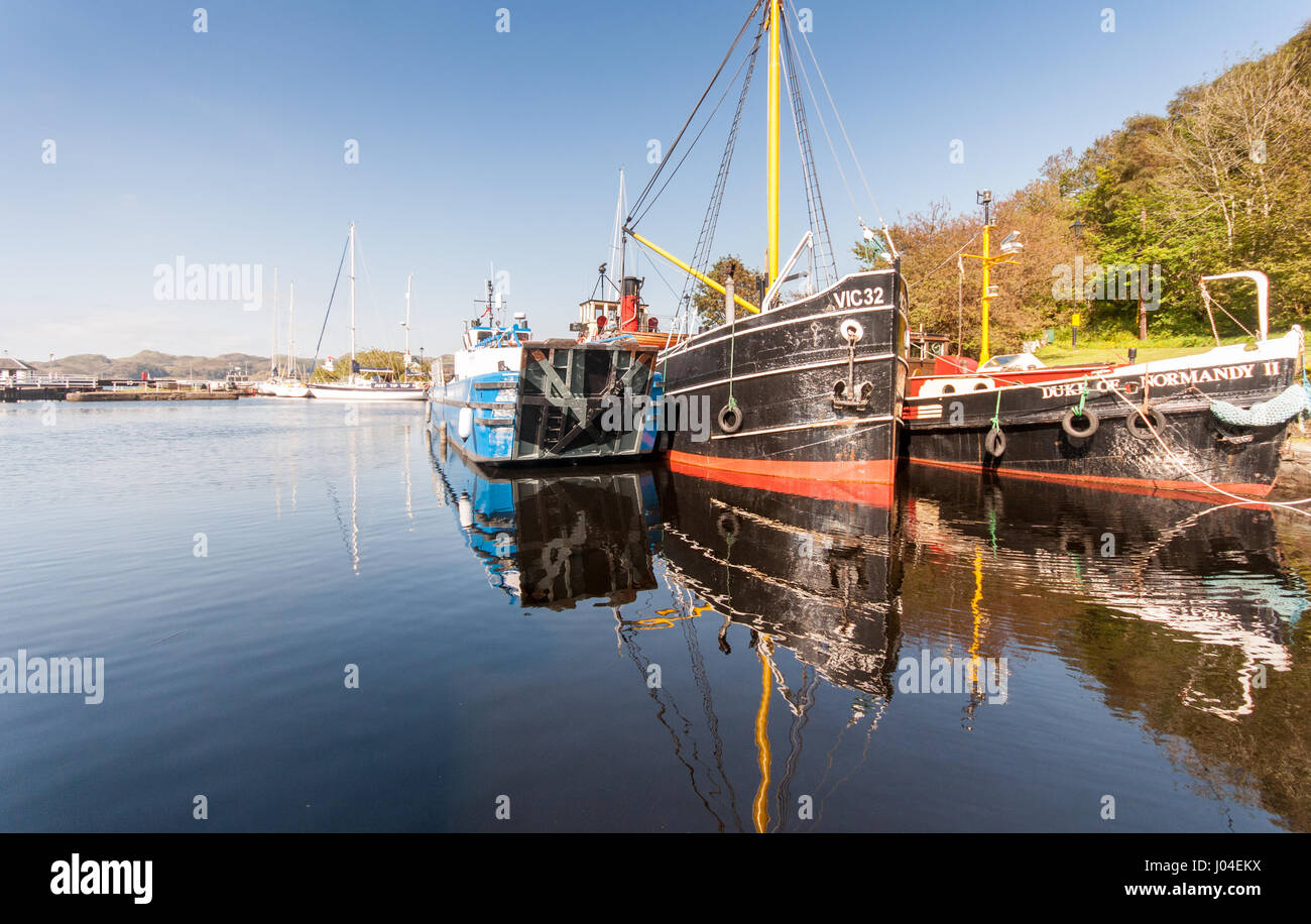 Crinan, Scotland, UK - June 3, 2011: The Vital Spark Clyde Puffer and other boats sit docked in the basin of the - Stock Image
