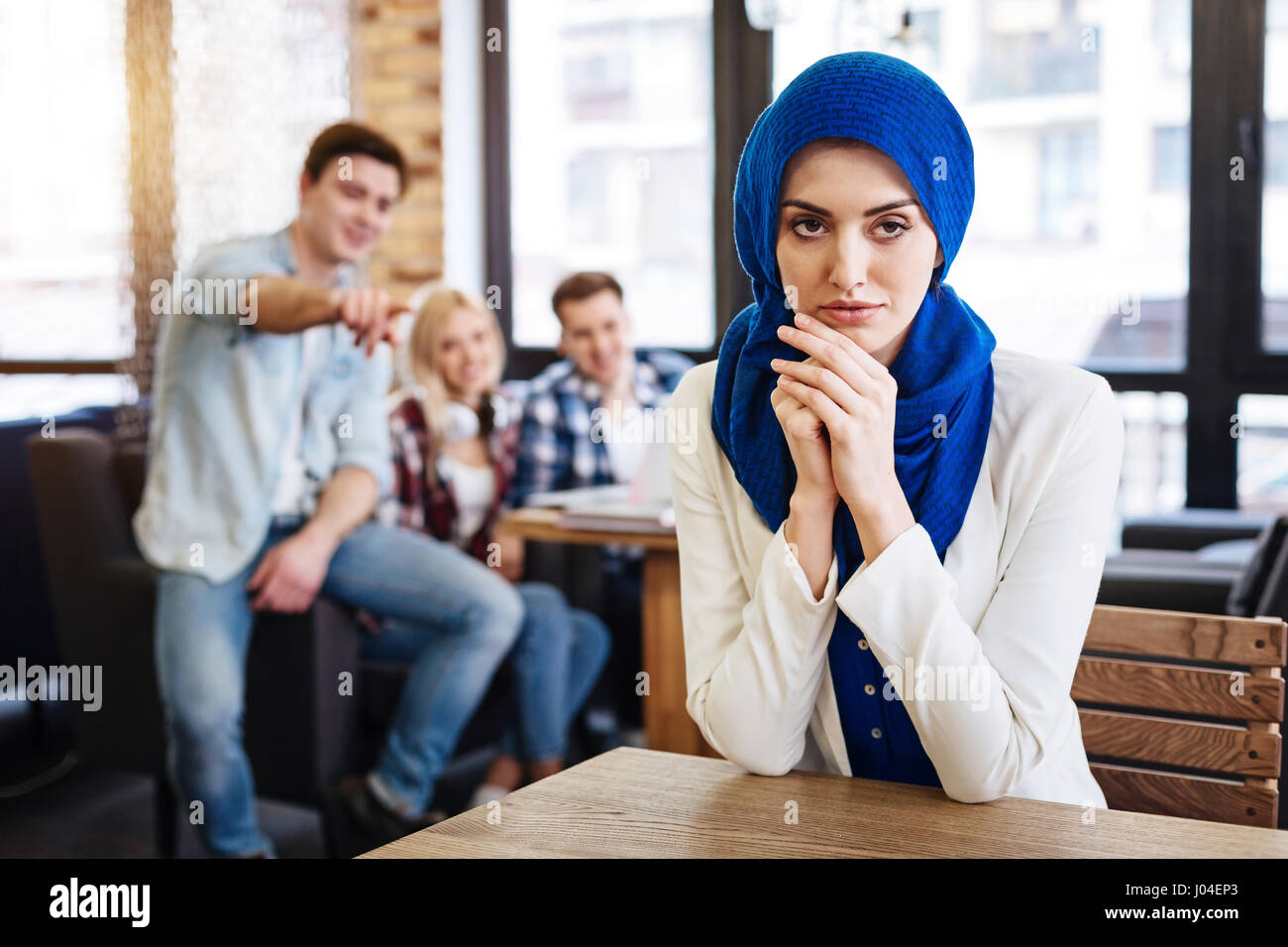 Beautiful pleasant muslim woman sitting in the cafe - Stock Image