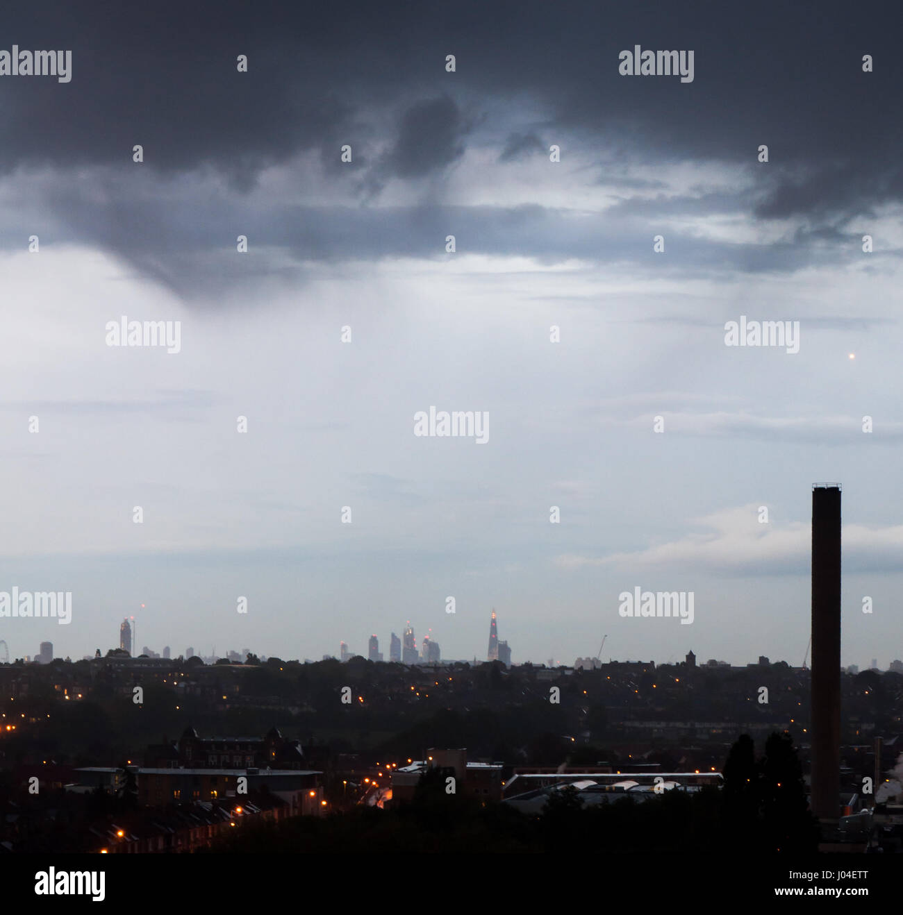 The distant City of London skyline seen from the south London suburb of Tooting. - Stock Image