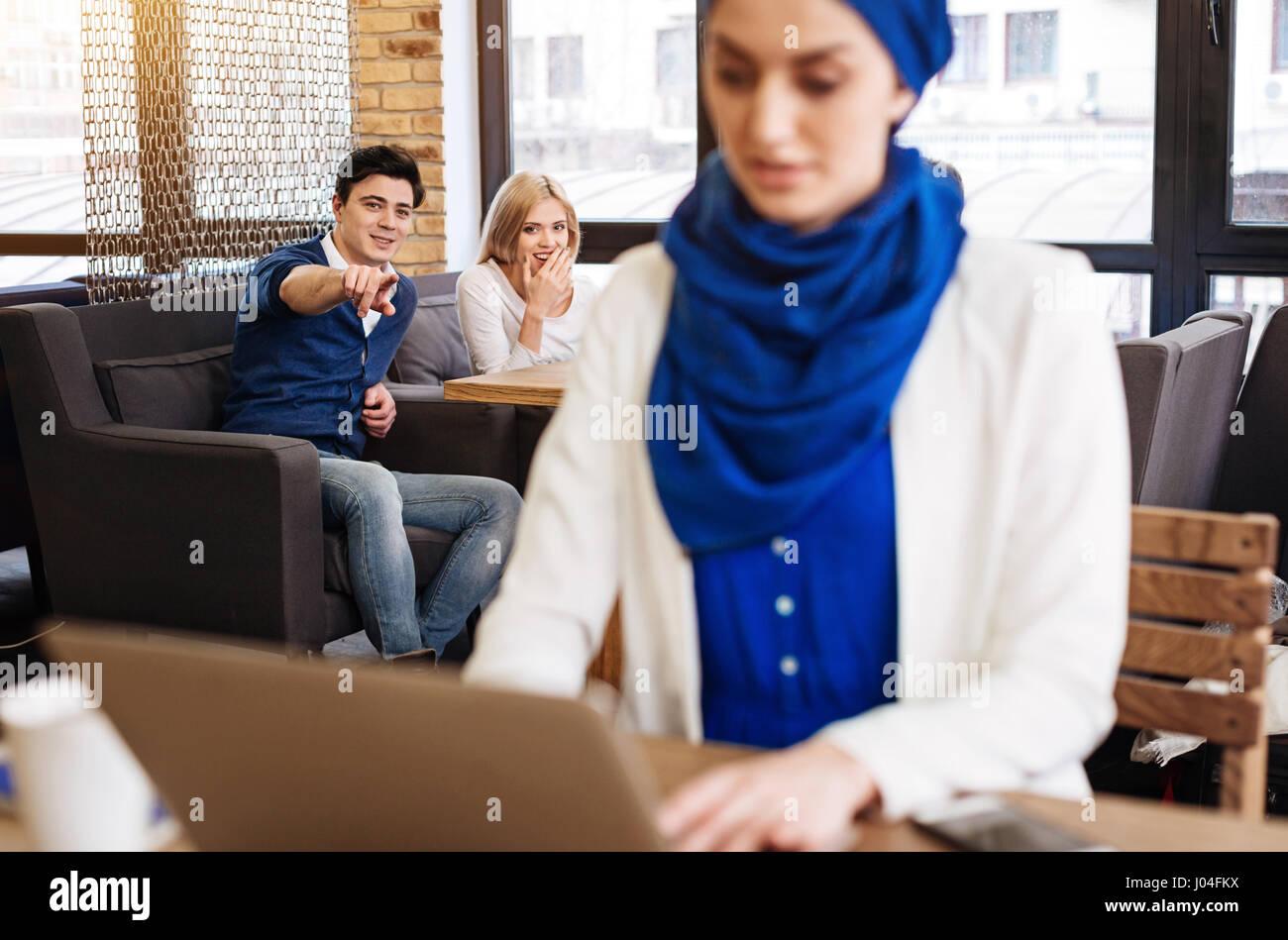 Joyful students humiliating muslim woman - Stock Image