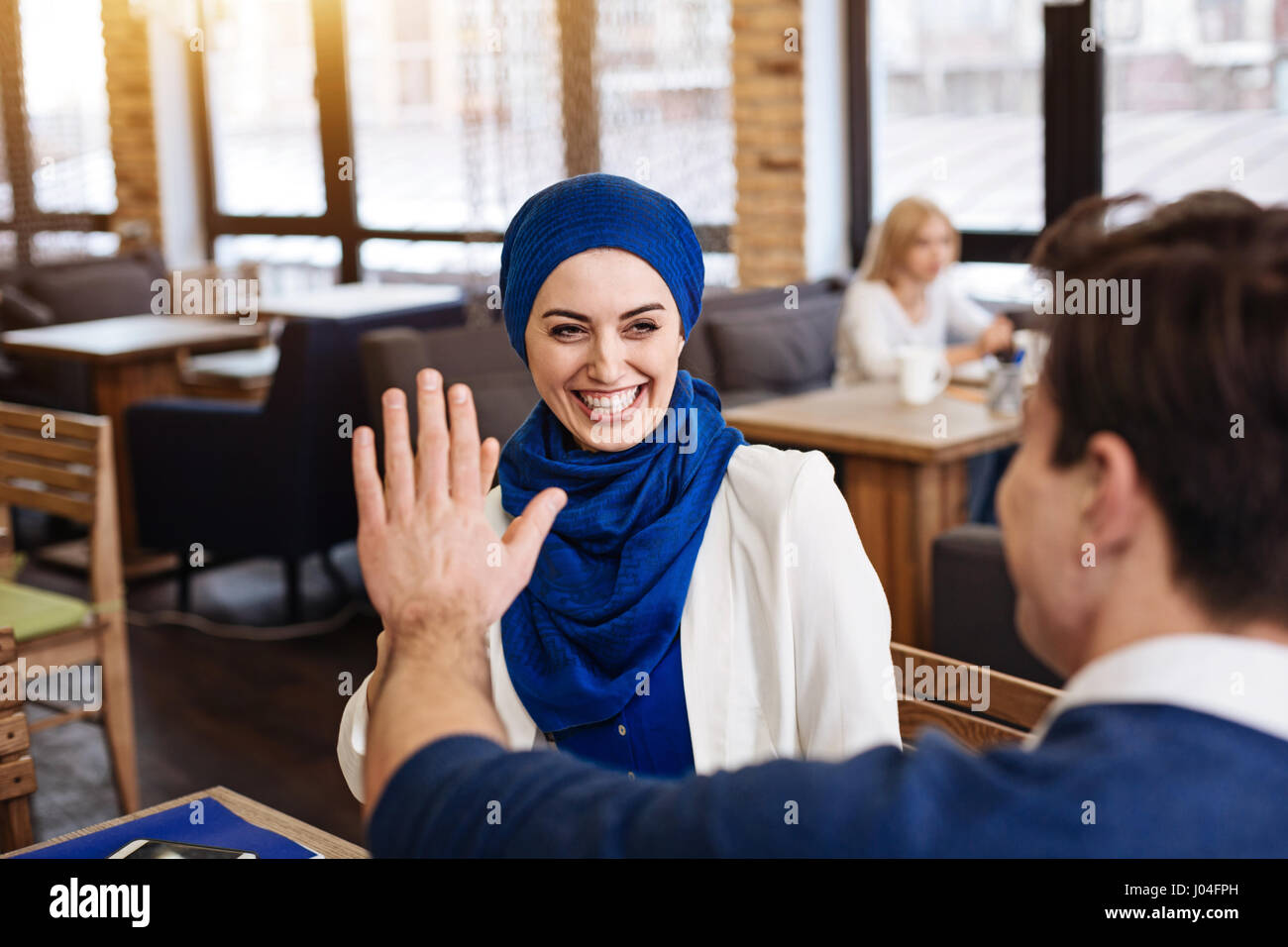 Cheerful businesscolleagues sitting in the cafe - Stock Image
