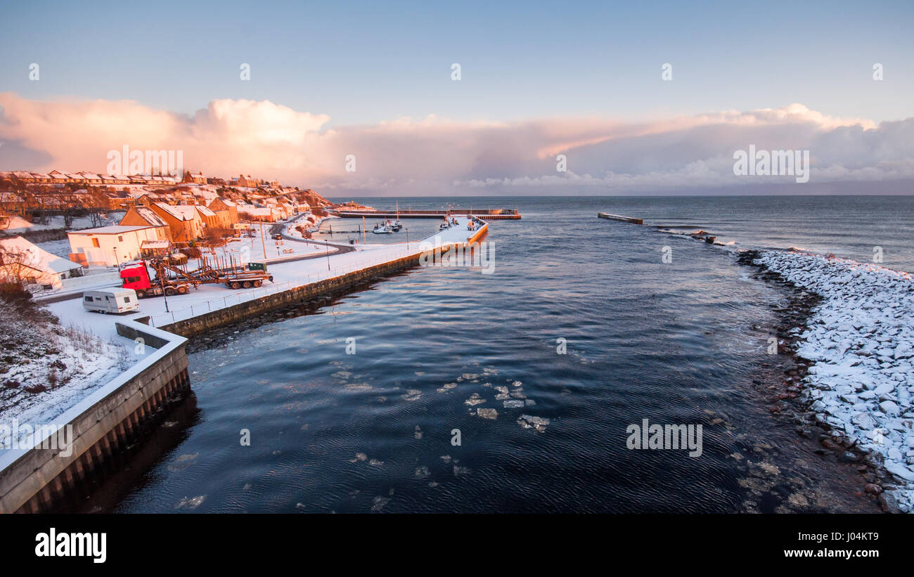 Snow lies on the village and sea wall of Helmsdale Harbour, and the banks of the Helmsdale River, on the Moray Firth - Stock Image