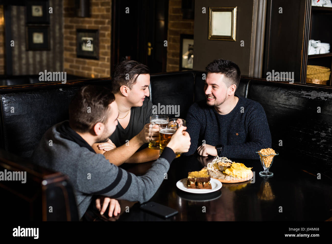 Three man friends drink beer and eat in traditional england pub. Meet friends in pub - Stock Image