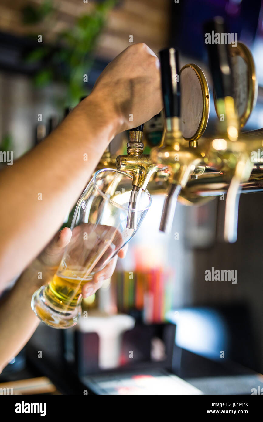 Mans hand pouring pint of beer behind the bar - Stock Image