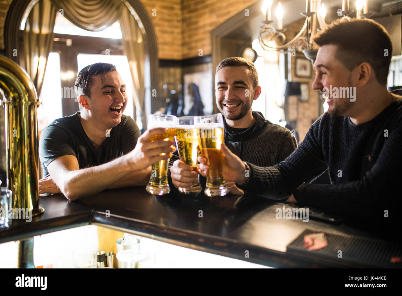 Three happy young men in casual wear talking and drinking beer while sitting at the bar counter together - Stock Image