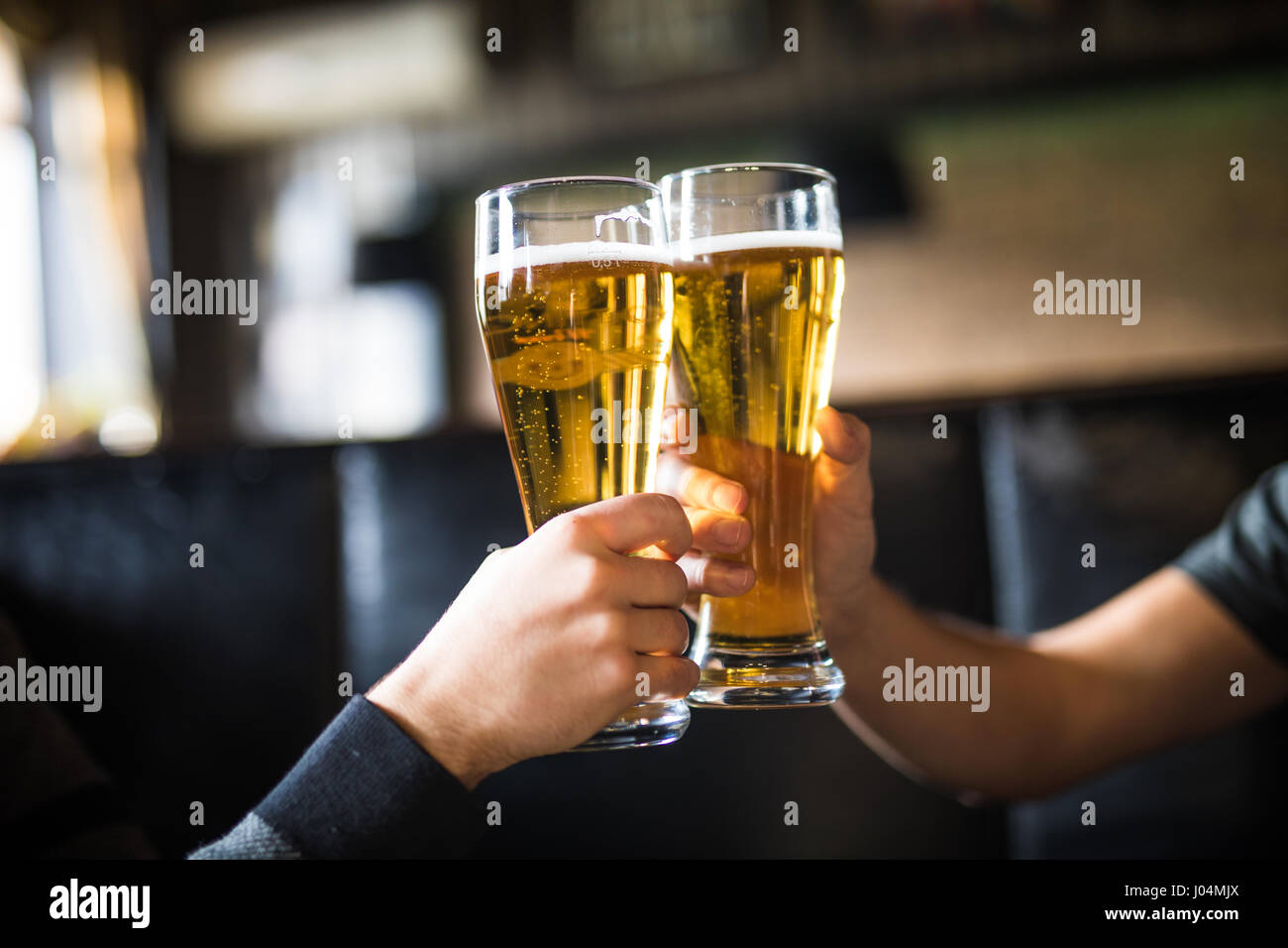 Close-up of two men in shirts toasting with beer at the bar counter - Stock Image