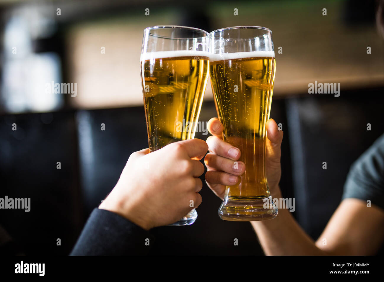 Men cheers with beer in glasses in pub. Stock Photo