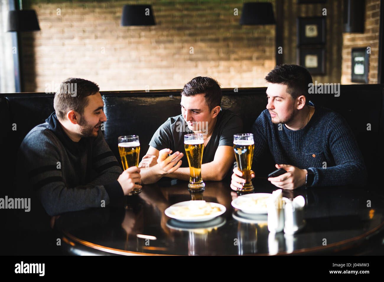 Three young men in casual clothes are talking, eating chips and drinking beer while sitting in pub, close-up - Stock Image