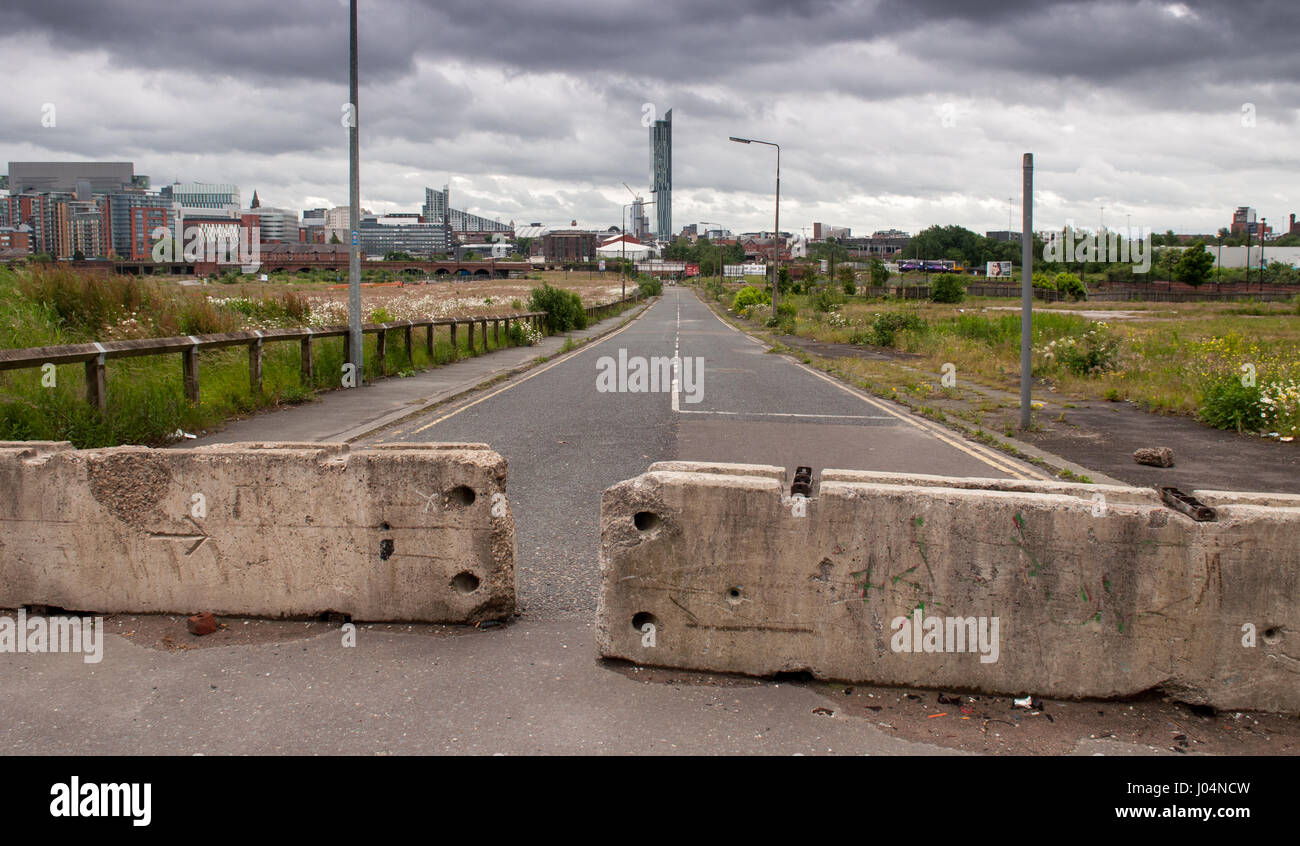 Concrete barriers block a street in the City of Salford borough of Greater Manchester where housing has been demolished - Stock Image
