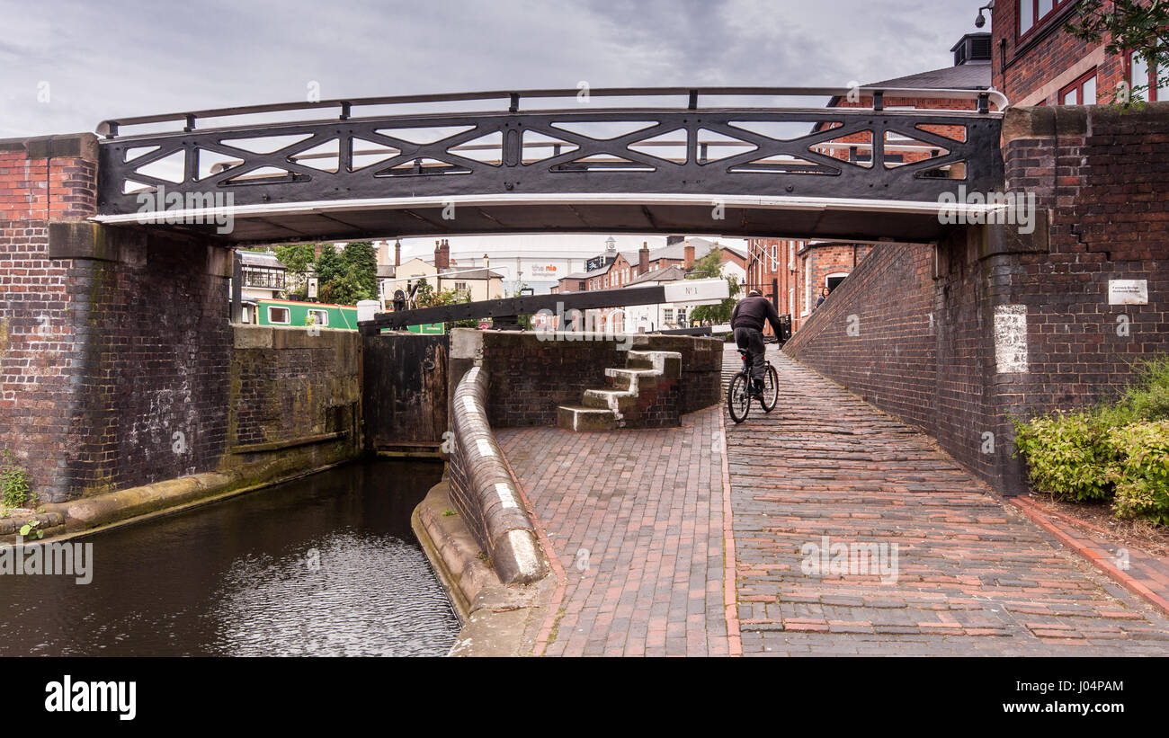 Birmingham, England, UK - June 23, 2012: A cyclist rides on the towpath of the Birmingham and Fazeley Canal, past - Stock Image