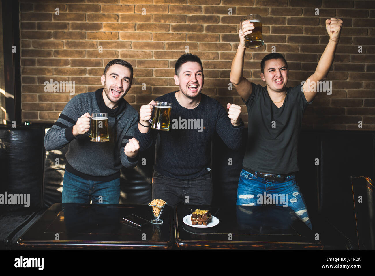 Three men with beer rejoice the victory of their favorite team in the pub - Stock Image