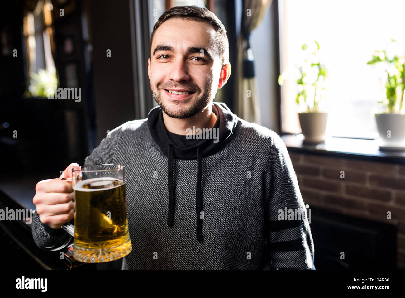 single man in a pub or bar holding the beer high in the air - Stock Image