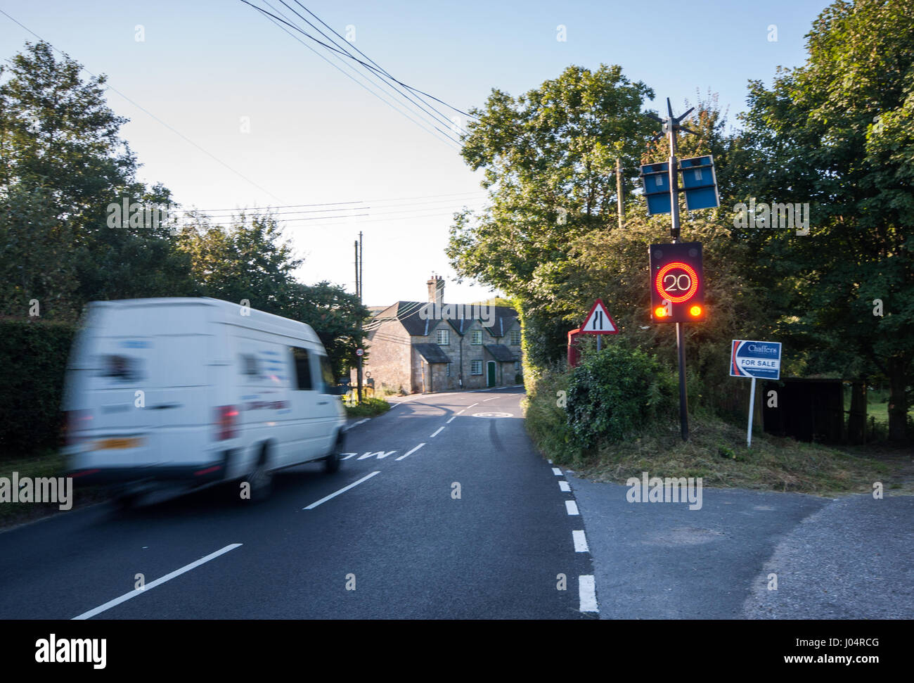 Shaftesbury, England, UK - July 28, 2012: Traffic rushes through Melbury Abbas village in rural north Dorset, activating - Stock Image