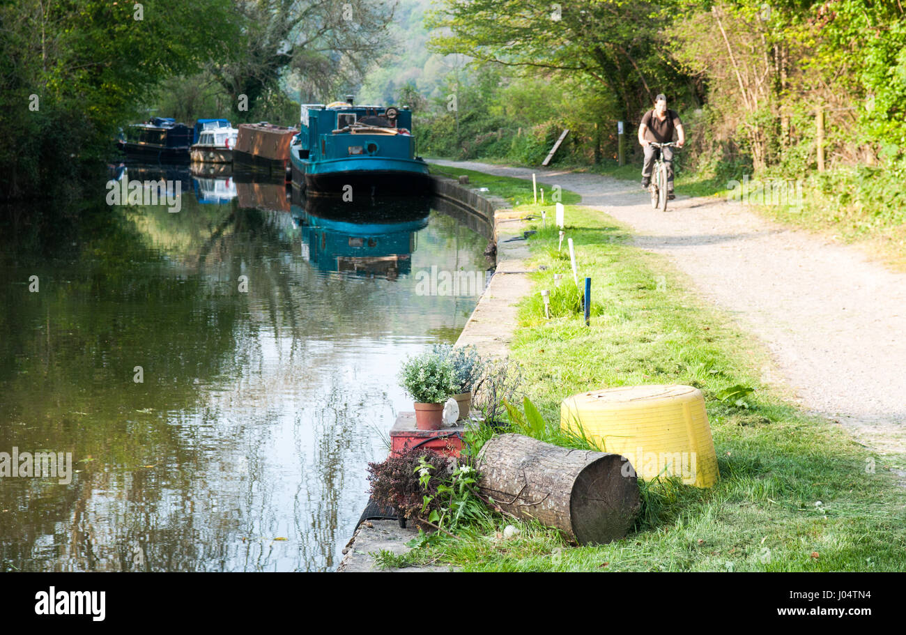 Bath, England - April 19, 2011: A cyclist passing boats on the Kennet & Avon Canal towpath near Bath in Somerset. - Stock Image