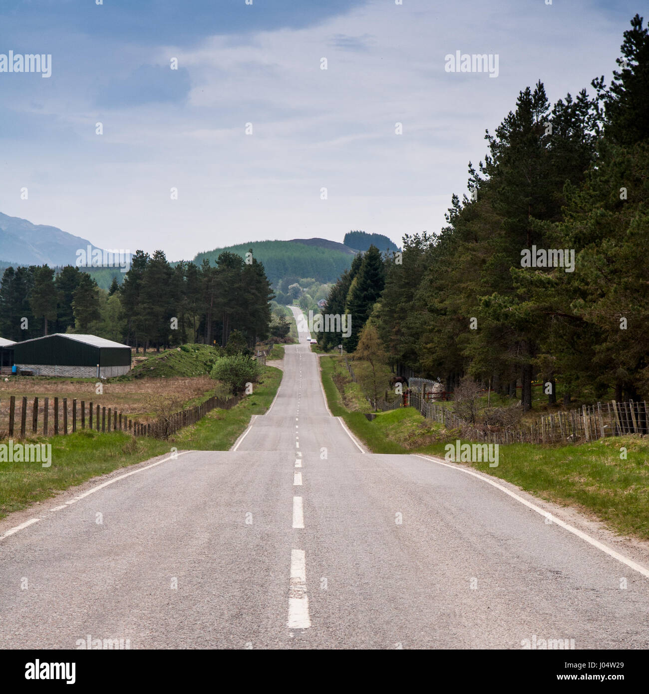 The long straight 18th century military road of General George Wade crosses remote undulating landscape of Stratherrick - Stock Image