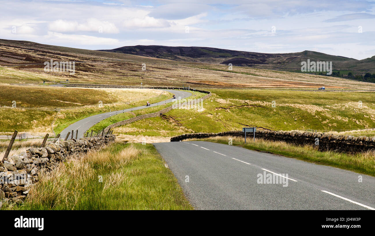 The two-lane B6276 road meanders through rolling moorland in Teesdale, County Durham, in England's North Pennines. - Stock Image