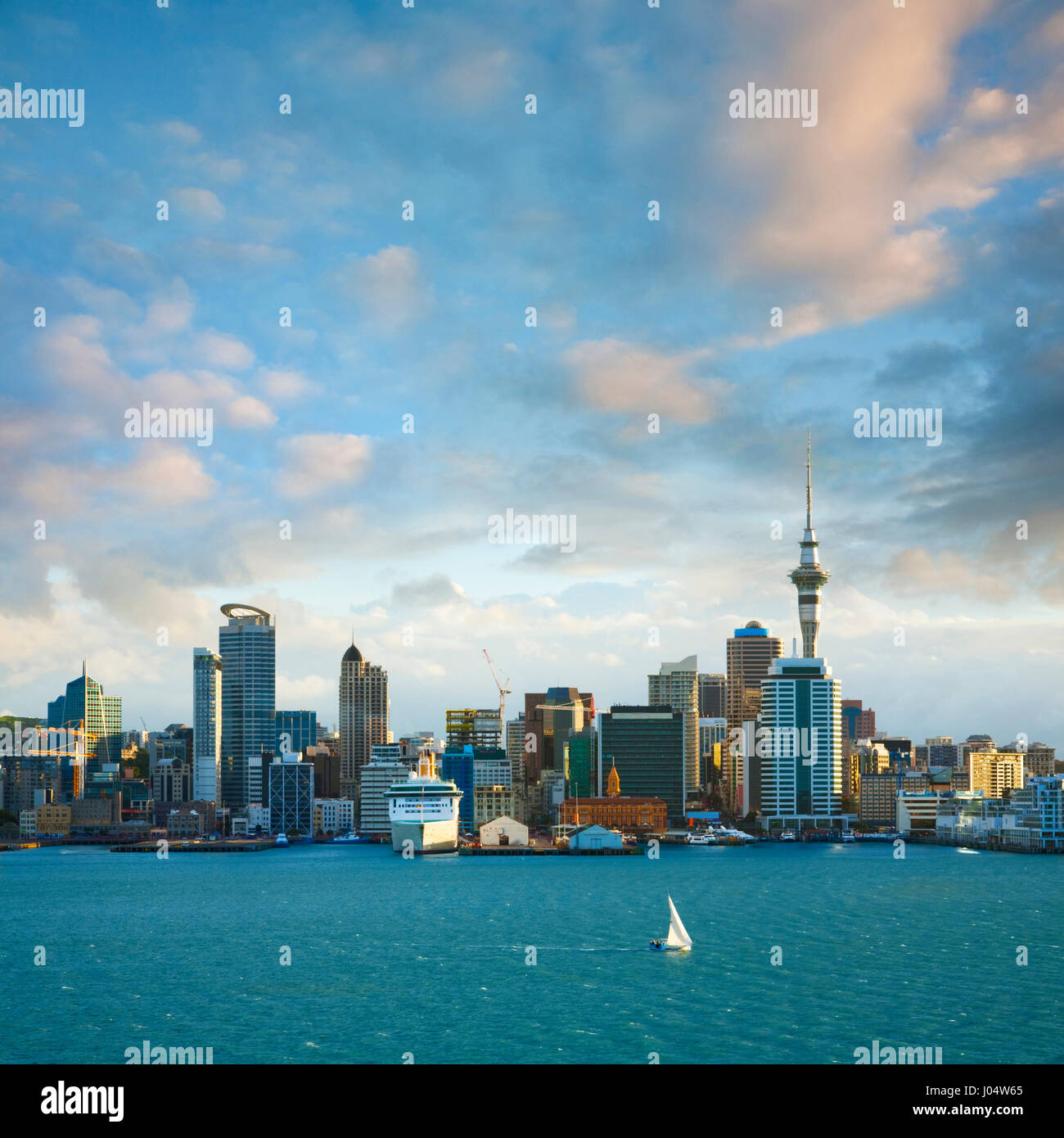 Auckland skyline in late afternoon light with a dramatic sky, just as the sun is low in the sky.  A sailing boat - Stock Image